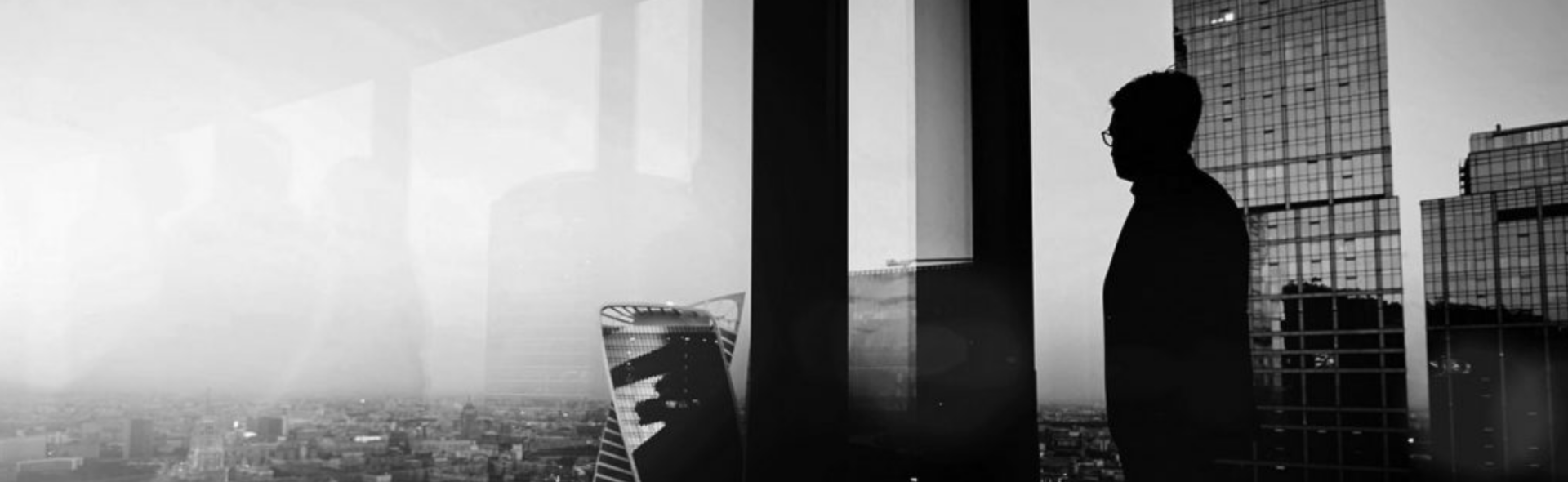 black and white image of man standing in high rise office building looking at city Knowledge Innovation Center