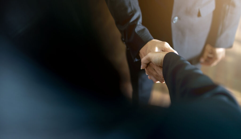 view of man and woman shaking hands for their partnership Knowledge Innovation Center